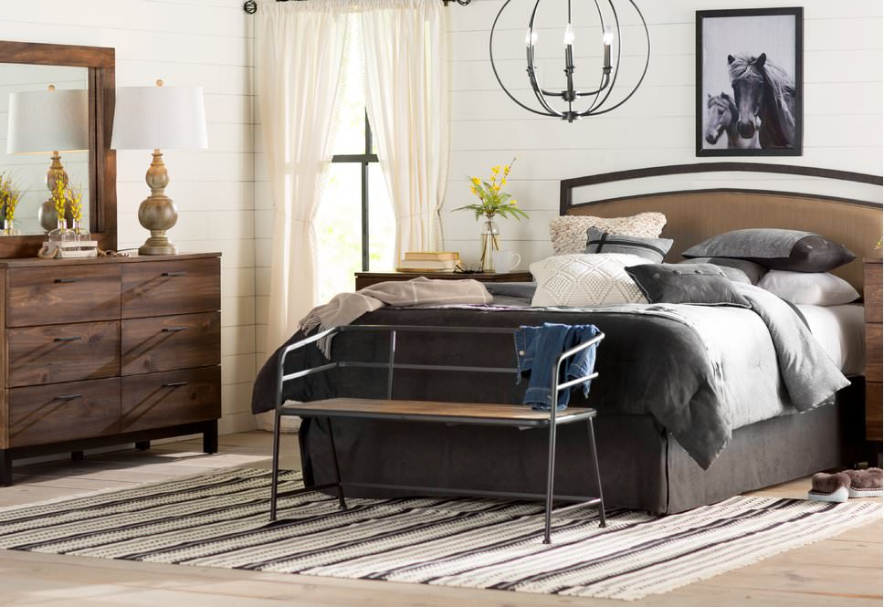 This primary bedroom is decorated with a horse wall art and a spherical chandelier that complements with the metal bench that sits on the edge of the bed.