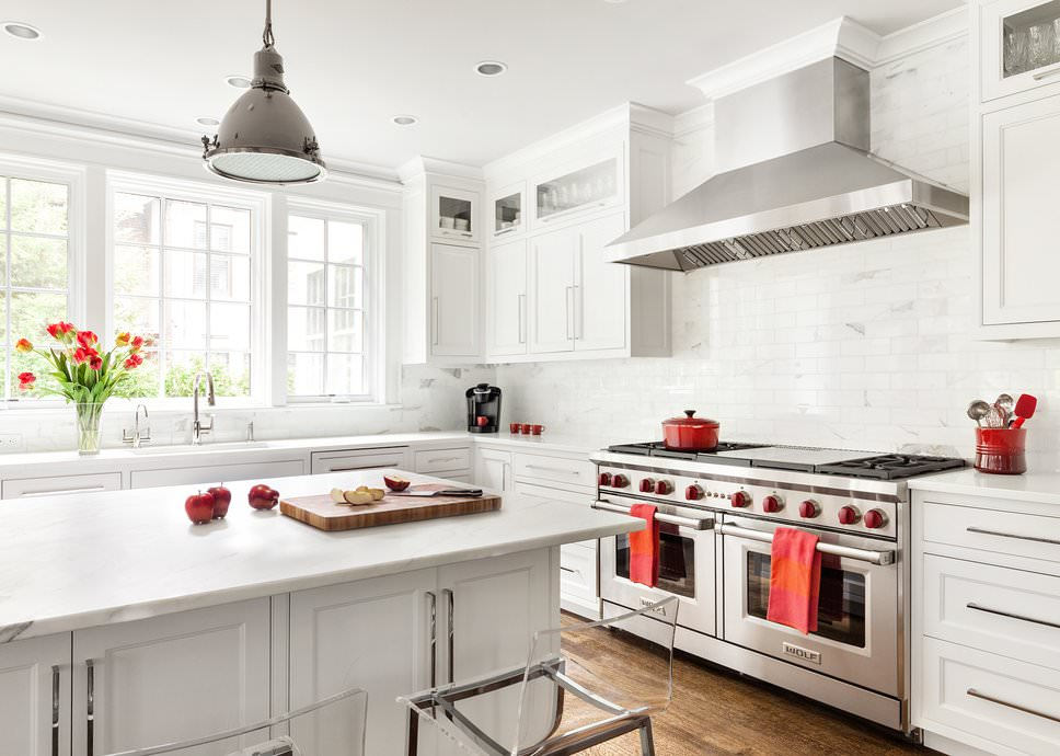 A large Scandinavian-Style kitchen featuring a hardwood flooring together with white backsplashes, cabinetry, kitchen counters and a center island, both are equipped with smooth white marble countertops.