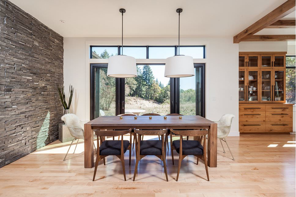 Light and airy dining room boasts a stone brick accent wall and light hardwood flooring. It includes a wooden dining set surrounded with black cushioned chairs along with perforated accent chairs clad in white faux fur cover.