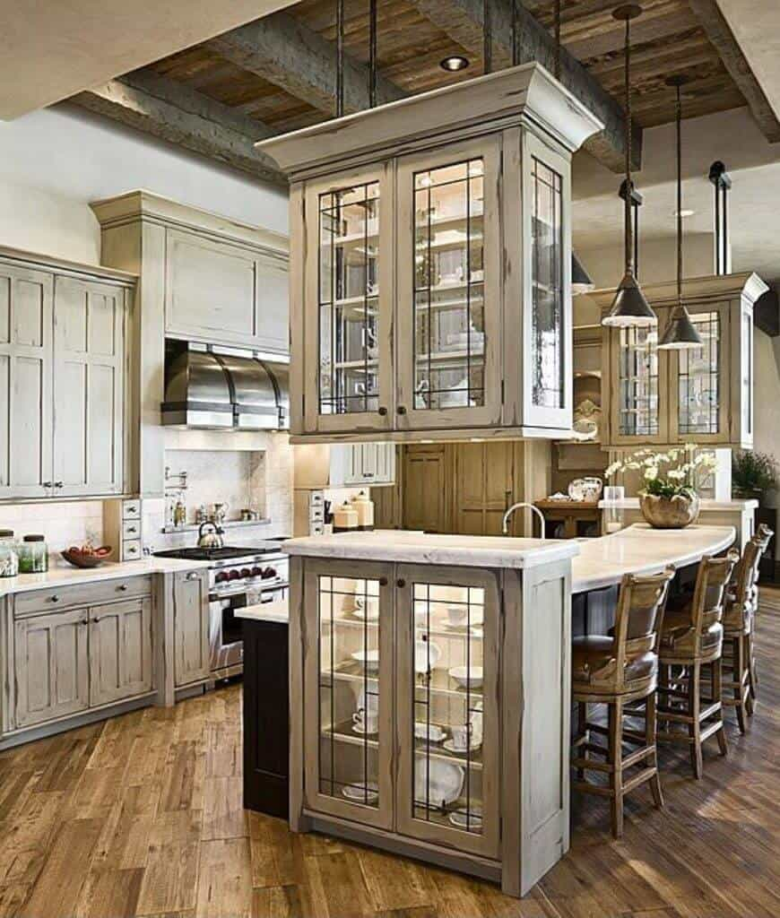 Rustic kitchen boasts wood plank flooring and wood beam ceiling with hanging black pendant lights and glass front cabinet. It has distressed cabinetry and a curved island bar paired with wooden counter chairs.