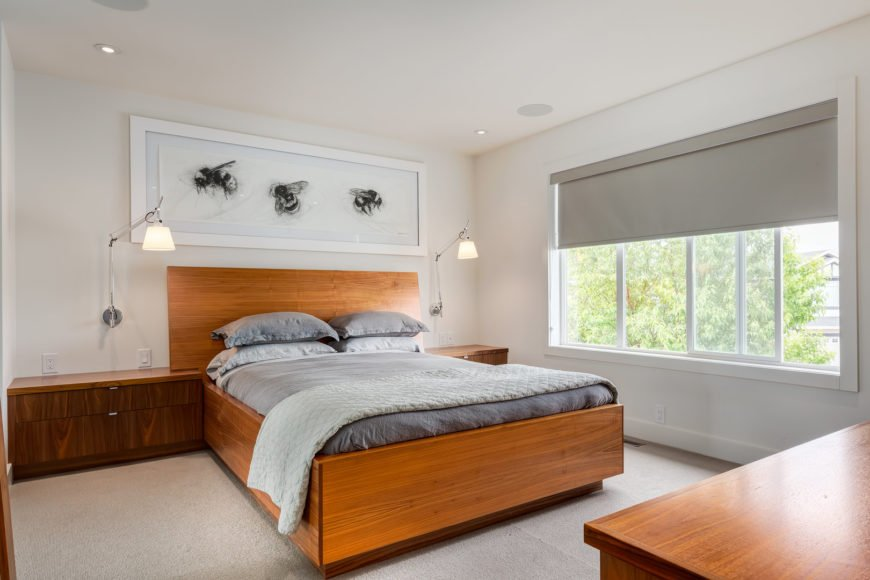 A master bedroom features a wooden bed that matches the nightstands.  It is decorated with a rectangular bee wall art along with modern wall sconces.