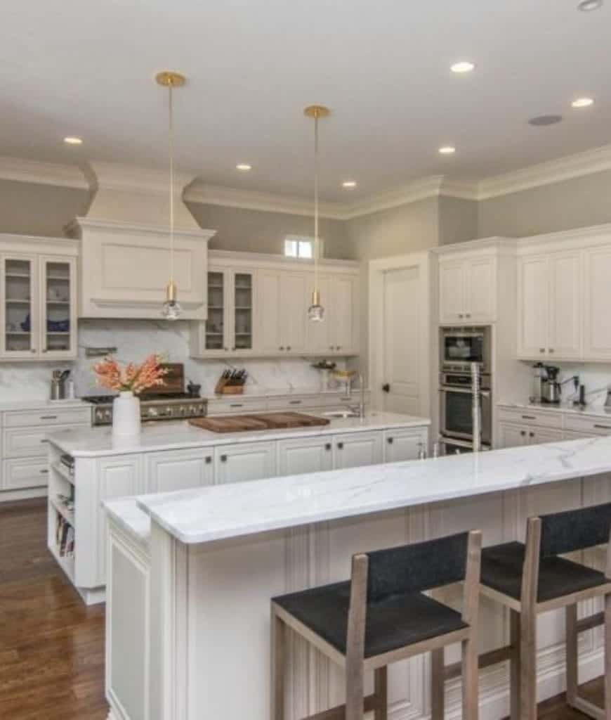 Gourmet kitchen features white vent hood and double island bars illuminated by mini globe pendants and recessed ceiling lights.