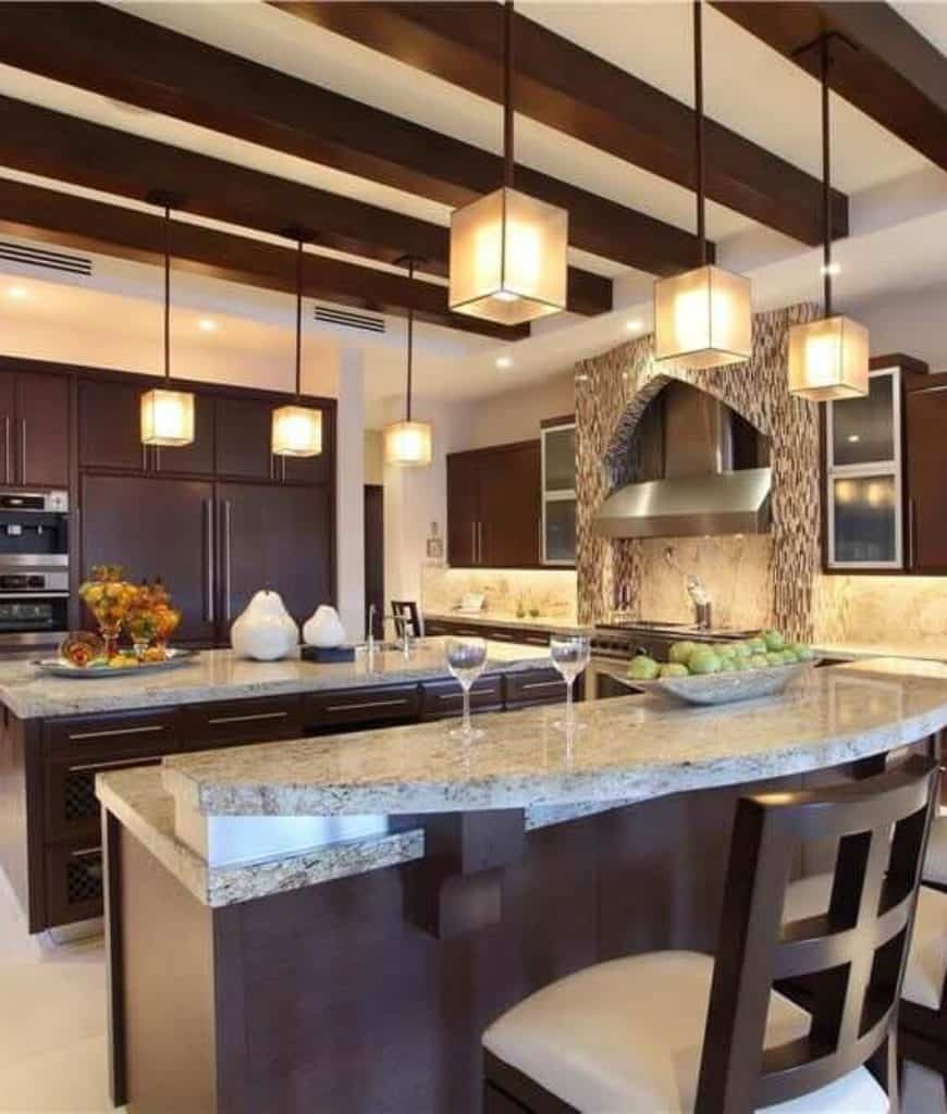 Cube pendant lights illuminate this kitchen boasting double breakfast bars topped with marble counters that complement with the backsplash tiles.