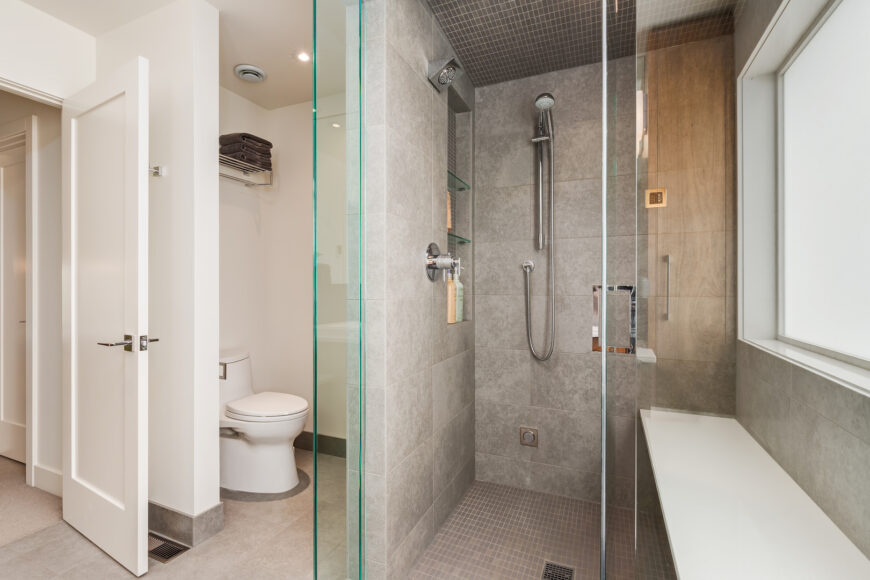 Contemporary primary bathroom with a gray tiled walk-in shower and white toilet area with marble flooring. It has a built-in seat nook beneath the frosted glass window.