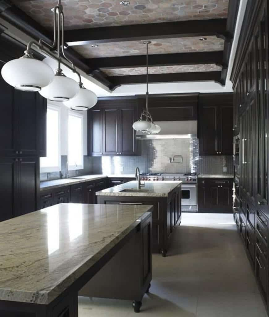 This kitchen is filled with dark wood cabinetry and matching double kitchen islands contrasted with white pendants that hung from the hex tiled ceiling framed with wood beams.