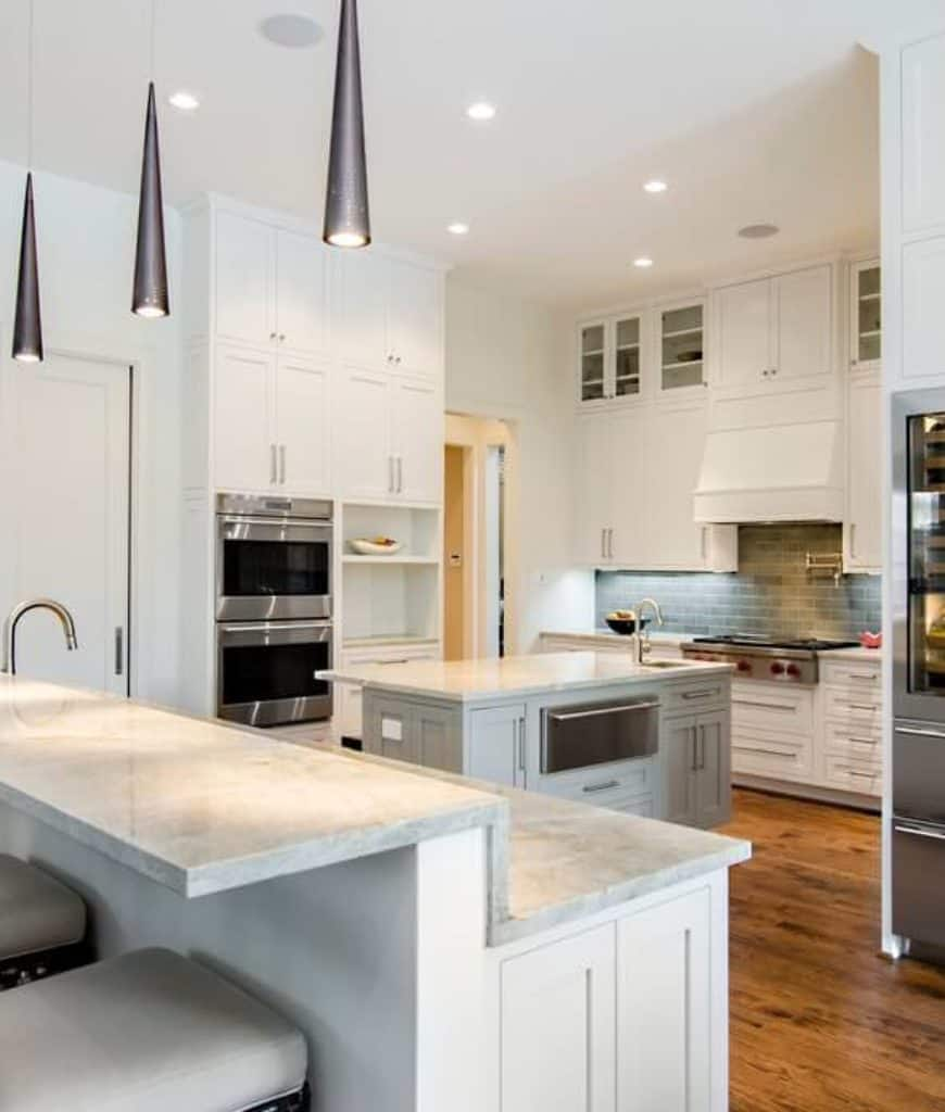 Stylish pendant lights hang over the two-tier peninsula in this kitchen with a marble top central island surrounded by white cabinetry and stainless steel appliances.