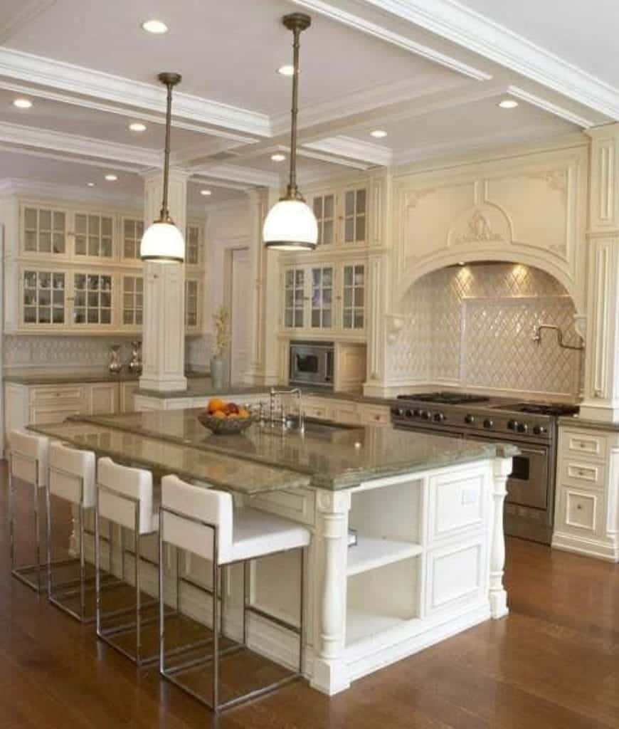 Elegant white kitchen with hardwood flooring and coffered ceiling mounted with recessed lights and glass pendants. It has ornate range alcove and a breakfast bar lined with white counter chairs.