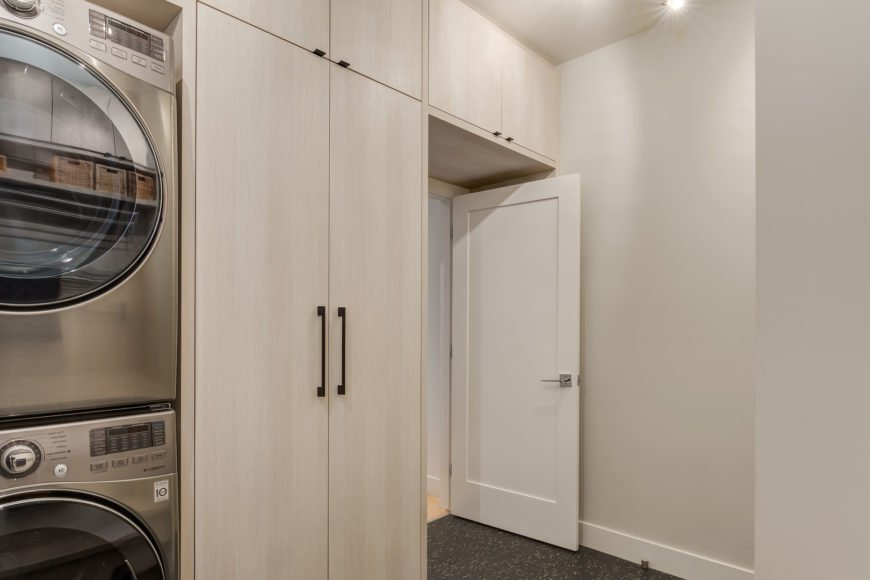 White laundry room featuring modish cabinetry and a stainless steel washer and dryer combo.