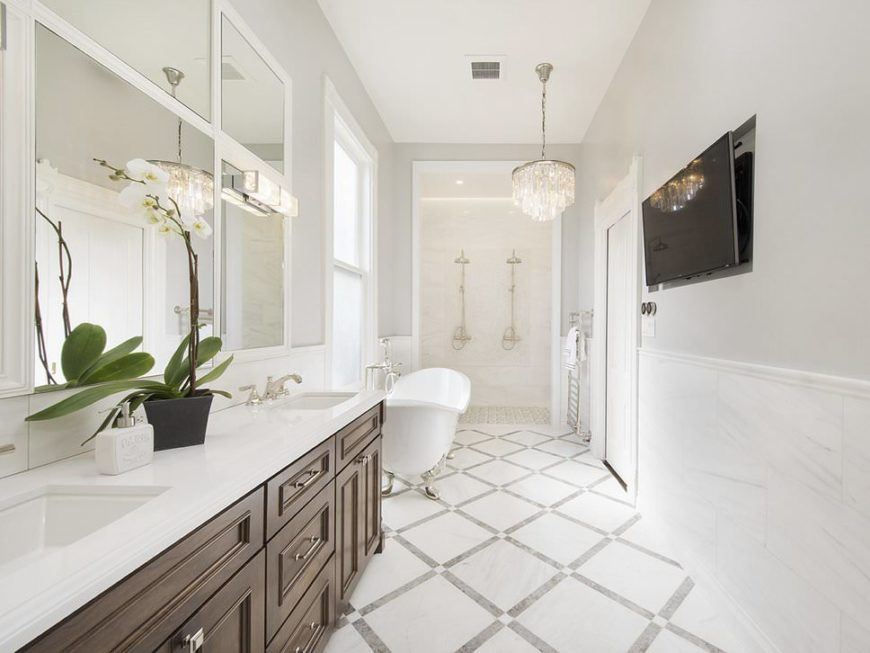 This primary bathroom offers a glamorous chandelier showering the beautiful floors and walls with elegant light. There's a freestanding tub and an open shower room.