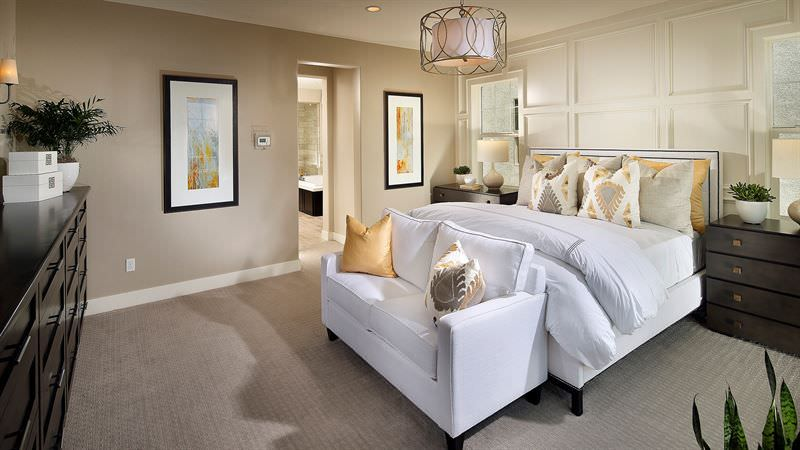 A lovely drum chandelier hung over the white bed with a loveseat on its end in this beige primary bedroom. It includes a full wainscoting accent wall fitted with a pair of windows covered in roman shades.