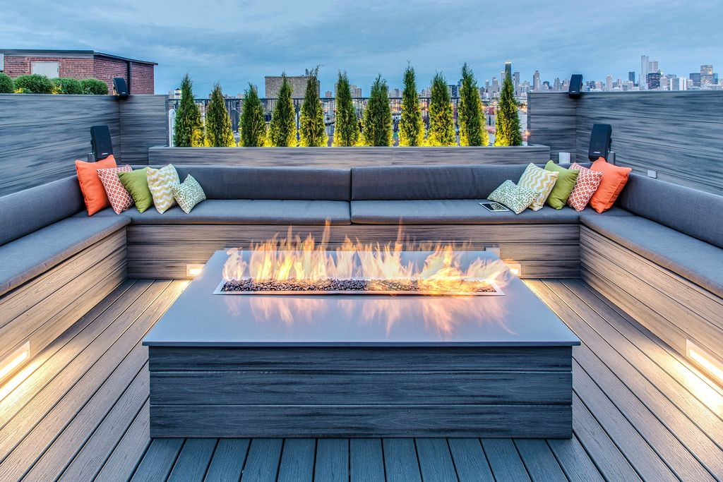 This modern deck boasts a custom fire pit surrounded by bench seating across the deck with throw pillows.