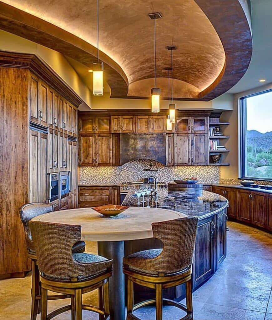 Magnificent kitchen features a semi-circular island bar attached with a round eating counter that's surrounded by classy wingback chairs. It is illuminated by pendant lights that hung from the barrel vaulted ceiling.