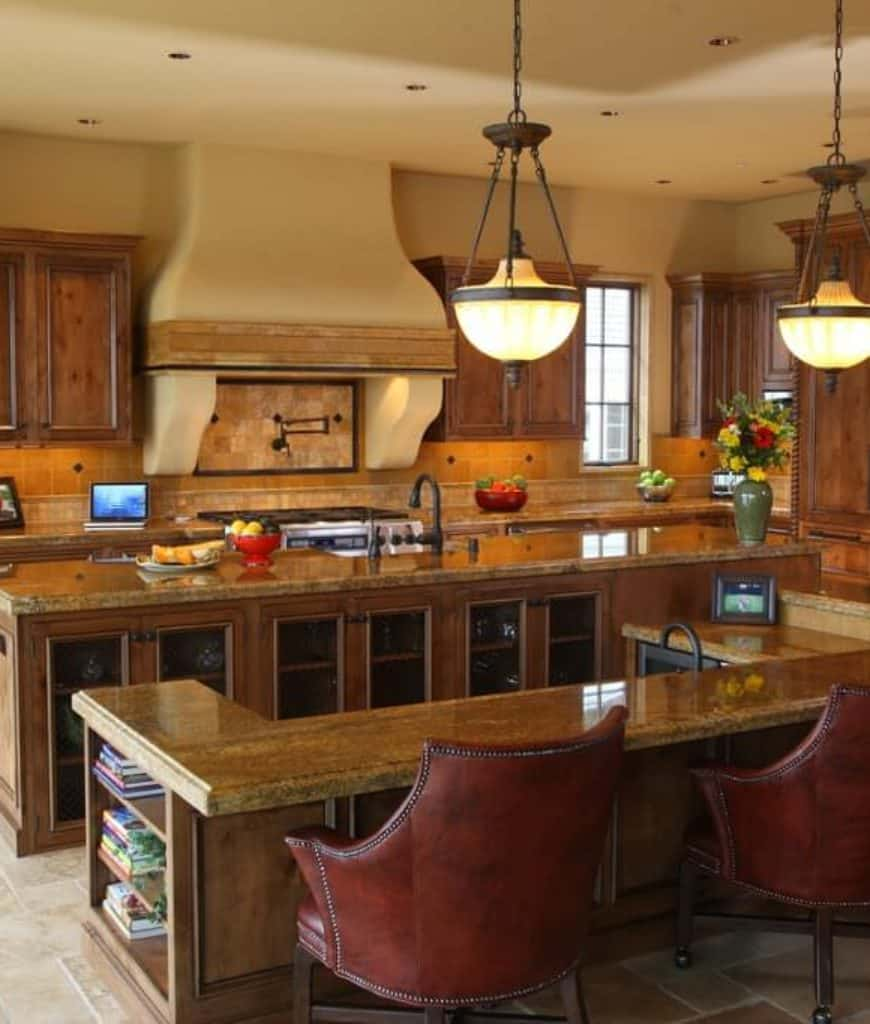 This kitchen boasts a wooden kitchen island attached with a U-shaped eating counter that's accompanied by brown leather chairs and vintage pendant lights.