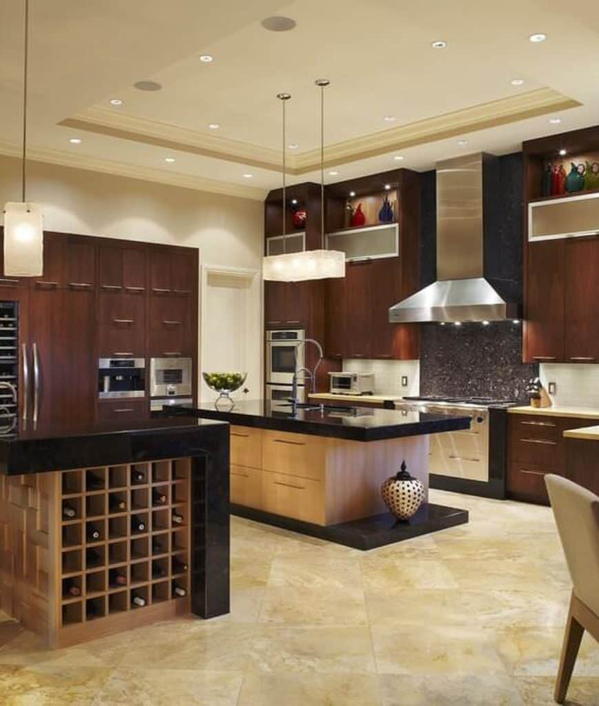 Gorgeous kitchen with dark wood cabinetry and double island bars topped with black granite counters and fitted with a sink and wine rack cubbies.