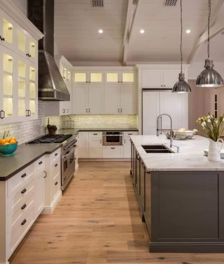 This kitchen offers a gray breakfast island lighted by chrome pendants and surrounded with white and glass front cabinetry fixed on the subway tile backsplash.