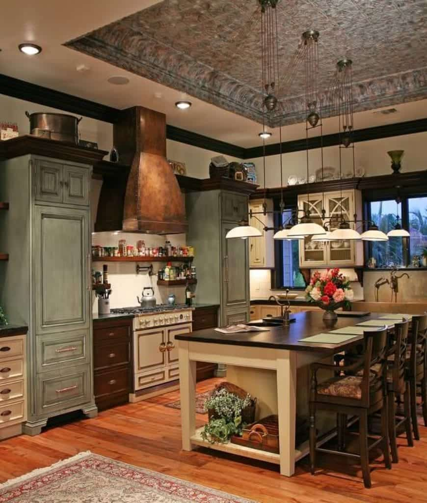 Wooden counter chairs sit at a white breakfast bar in this kitchen with distressed cabinetry and pendant lights that hung from the tray ceiling.