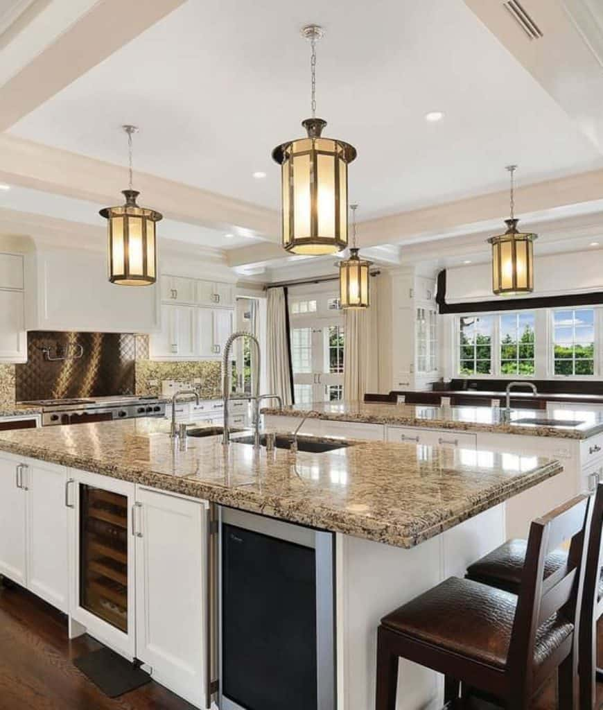 Deluxe kitchen with white framed windows and coffered ceiling mounted with recessed lights and stylish pendants. It includes double island bars fitted with sinks and wine fridge.