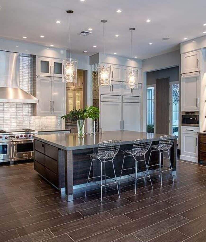 Spacious kitchen with gray cabinetry and a dark wood breakfast island lined with fancy pendant lights and metal counter chairs over wood plank flooring.