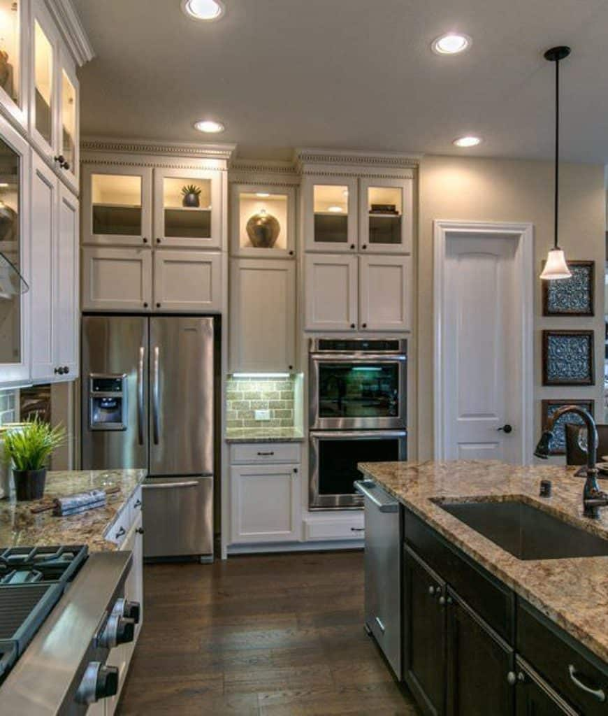 This kitchen boasts a granite top breakfast bar and white cabinetry with stainless steel appliances inset. It is illuminated by a glass pendant and recessed lights mounted on the white ceiling.