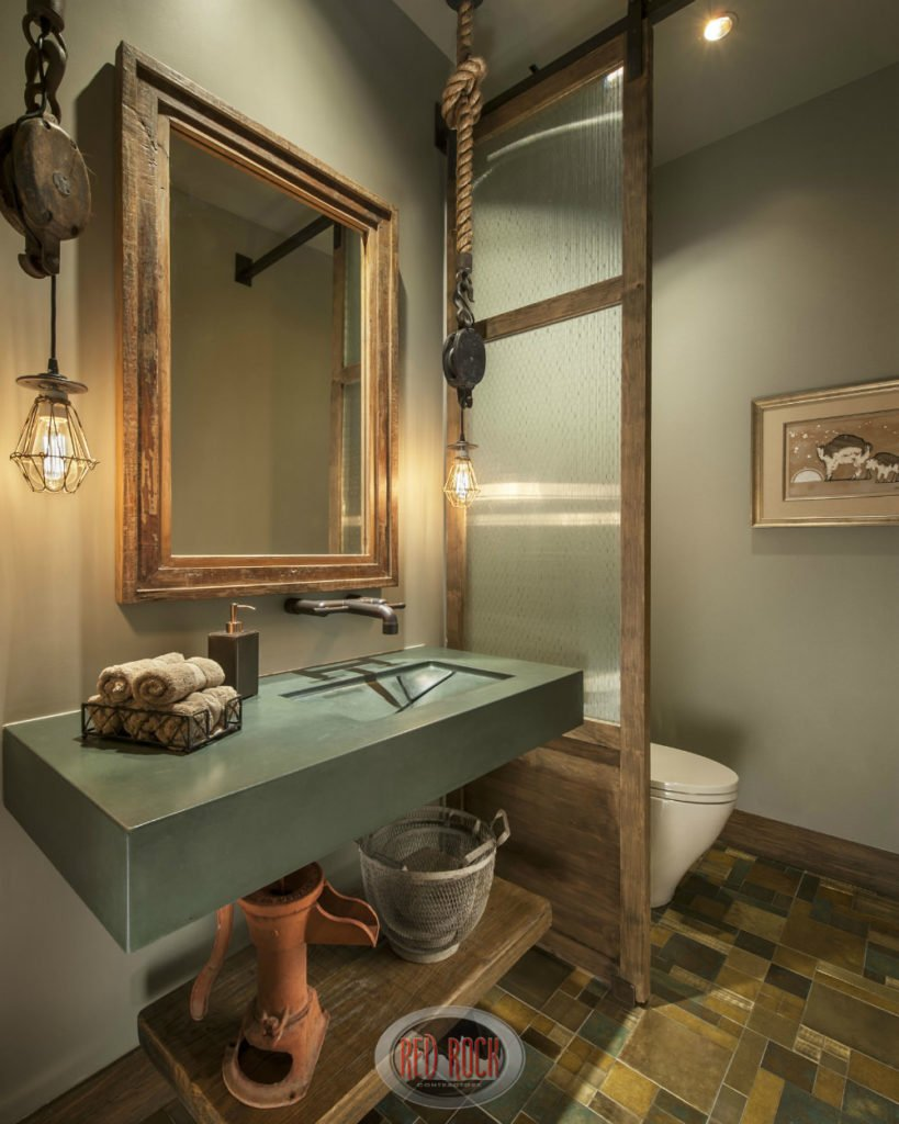 Rustic bathroom with a multi-colored tile flooring and a wooden divider fitted with frosted glass panels separating the toilet from the green sink vanity.