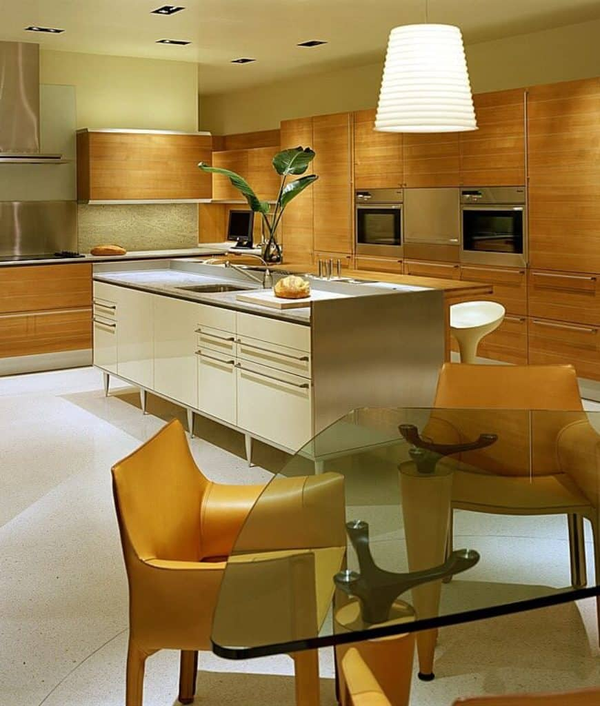 Warm eat-in kitchen showcases wooden cabinetry and a white central island along with a glass top dining table and stylish yellow chairs lighted by a large pendant.