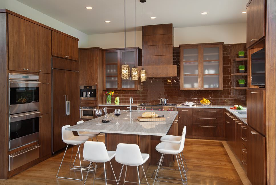 Brown themed U-shaped kitchen with wooden cabinets, wooden drawers, breakfast island in a marble countertop, hardwood floors, a combination of recessed lighting and grouped pendant lights.