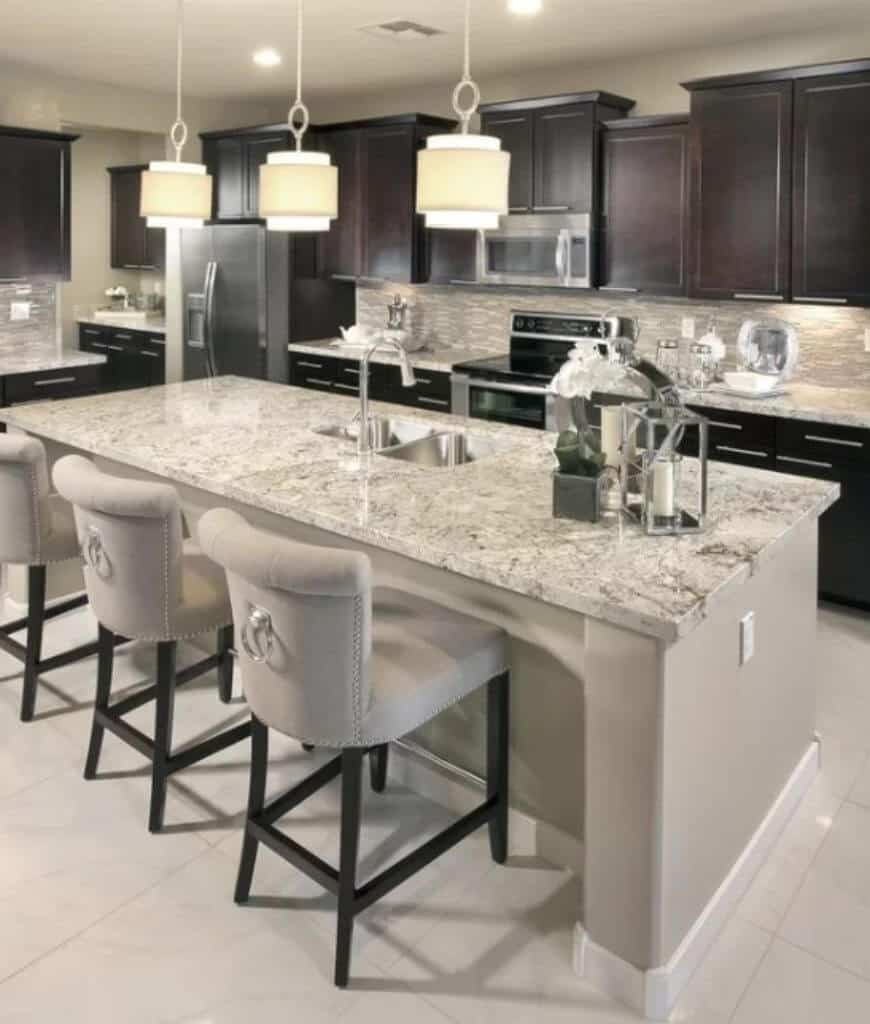 Transitional kitchen illuminated by stylish pendant lights that hung over the marble top island bar accompanied by gray upholstered chairs with rings.