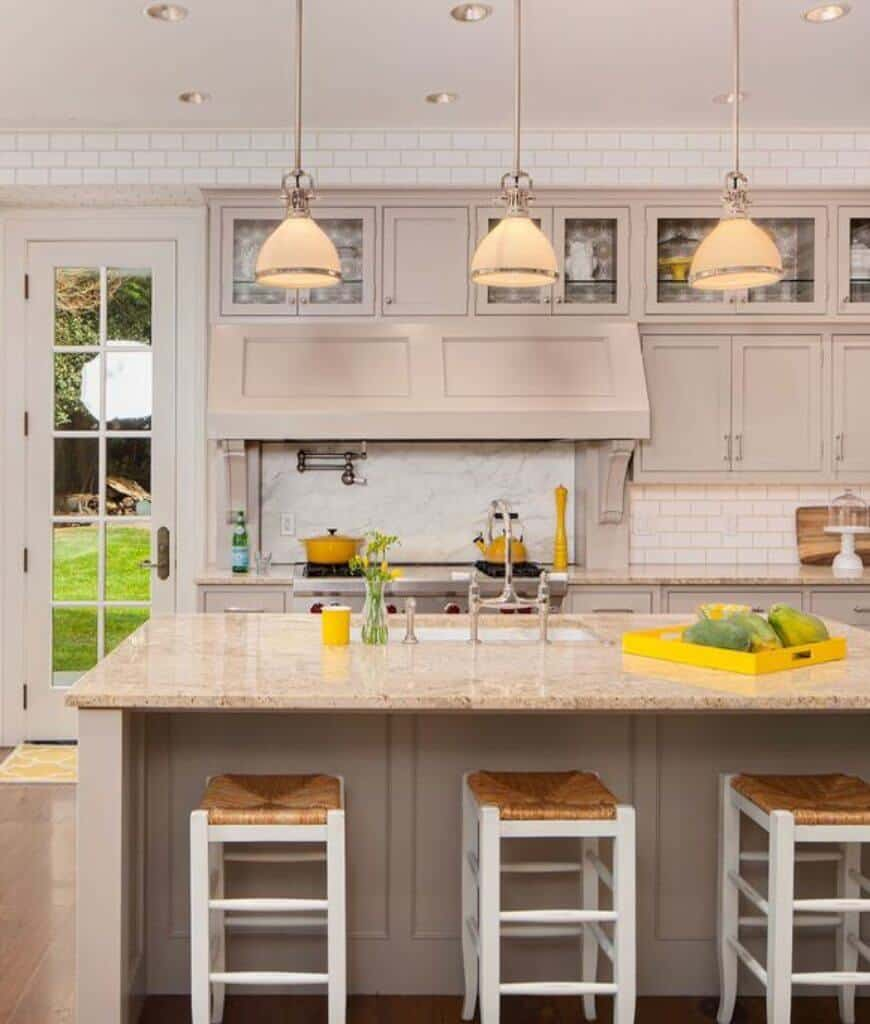 Classy kitchen with a subtle pop of color yellow offers a beige breakfast bar lined with white bar stools and glass dome pendants. It has white brick walls and a framed glass door that opens to the lush green yard.