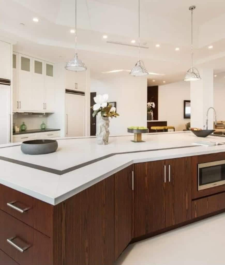 Bright kitchen illuminated by recessed ceiling lights and chrome pendants that hung over the wooden central island topped with quartz counter and sink.