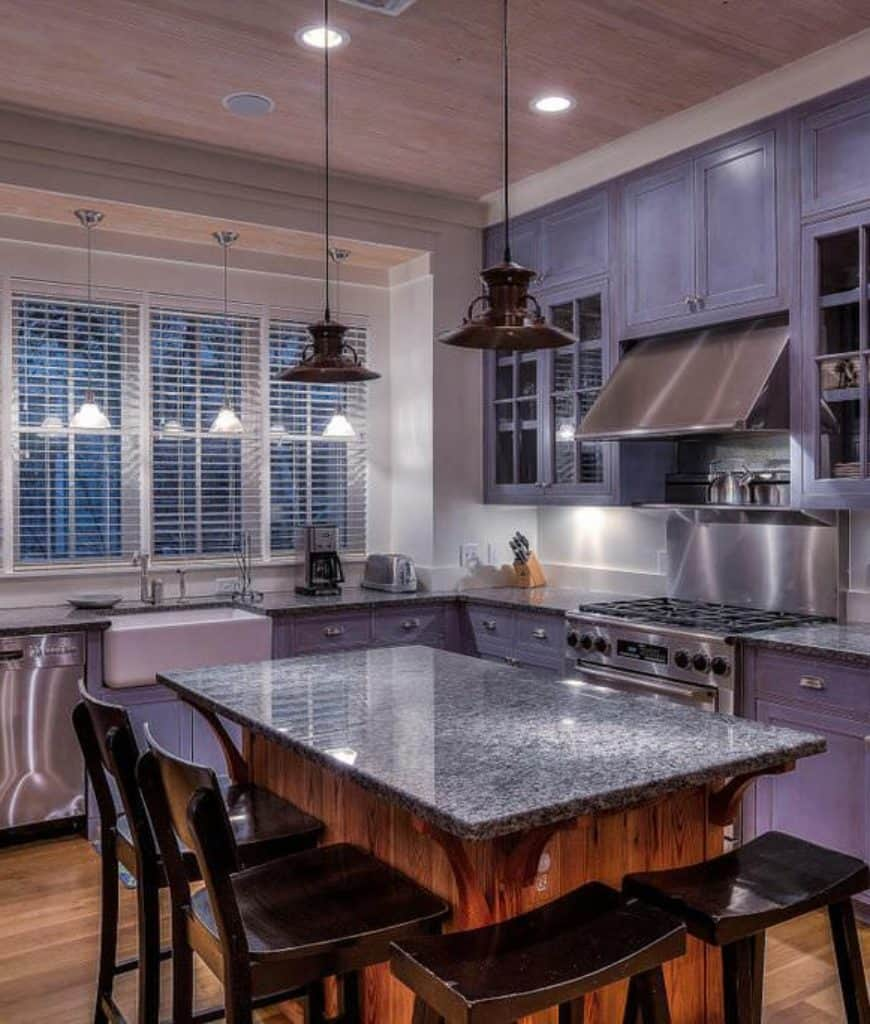This kitchen features stainless steel vent hood fixed in between glass front cabinets and a wooden central island surrounded with black stools and gray cabinetry.
