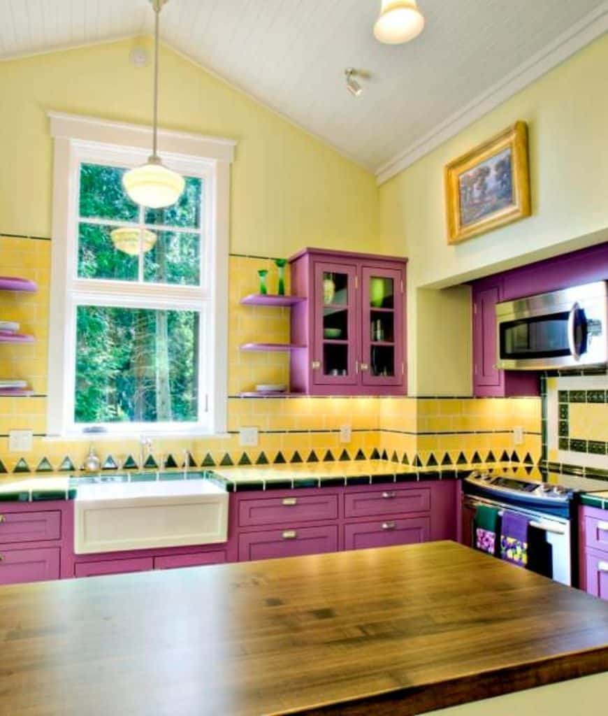 Lively kitchen with pink cabinetry and shelves mounted on the vibrant yellow tile backsplash. It includes a glazed window and a wooden breakfast bar illuminated by a pendant light that hung from the cathedral ceiling.