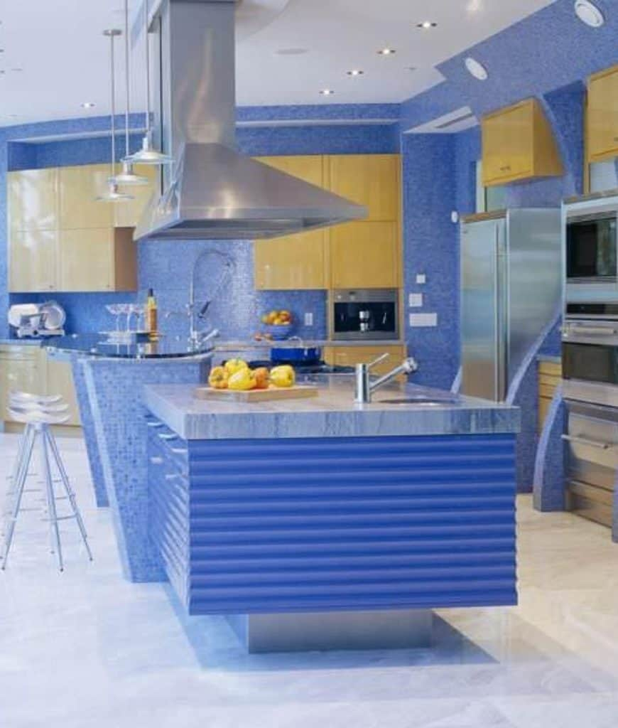 Charming blue kitchen boasts light wood cabinetry and an immense kitchen island with a raised eating counter lined with white stools and pendant lights.