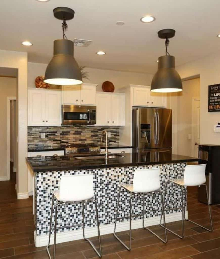 A pair of oversized black pendants illuminate this kitchen showcasing white cabinetry and a granite top central island clad in black and white mosaic tiles.