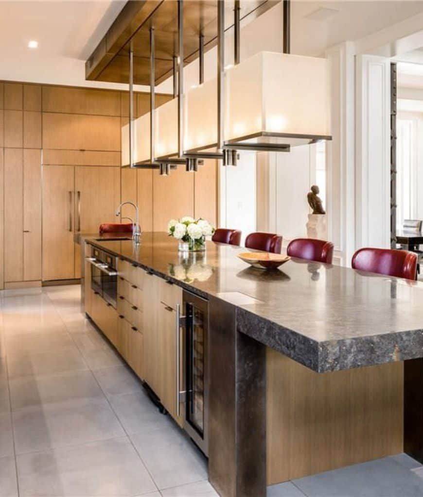 This kitchen features wooden storage cabinets that complement the breakfast island fitted with ovens and wine fridge. It is accompanied by a linear pendant light and red wingback chairs.