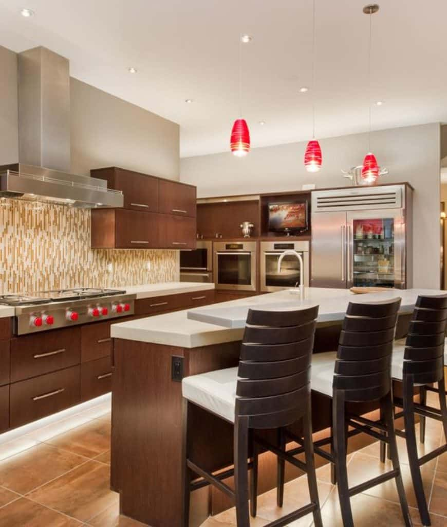 Sophisticated kitchen accented with red pendant lights that hung over the wooden island bar lined with white cushioned counter chairs.