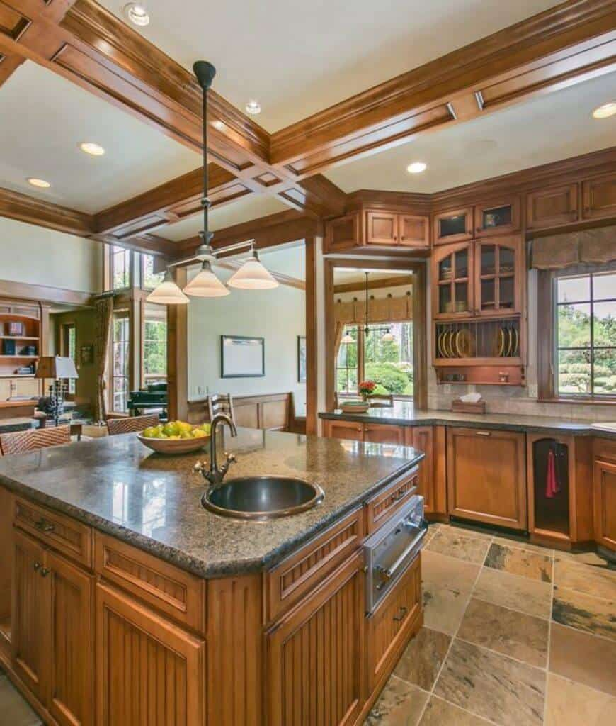 Craftsman kitchen showcases tiled flooring and coffered ceiling with a hanging pendant light. It has wooden cabinetry and matching beadboard kitchen island topped with granite counter and round sink.