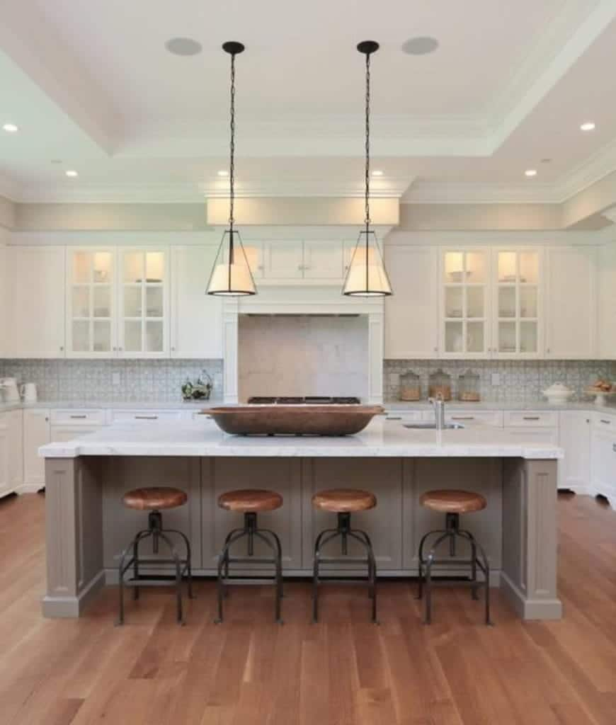 This kitchen is filled with white cabinetry and beige island bar lighted by a pair of pendant lights along with recessed lights mounted on the tray ceiling.
