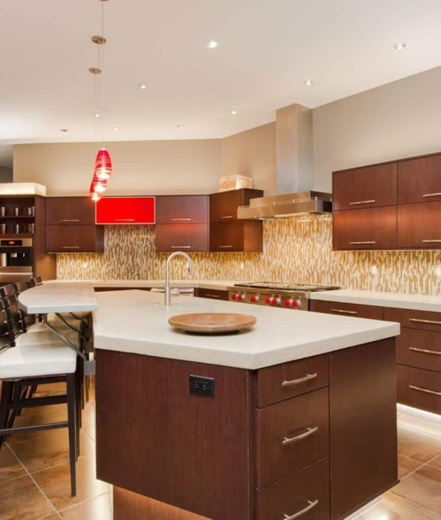 Stylish kitchen accented with an eye-catching backsplash and red cabinet complementing with the pendant lights that hung over a two-tier breakfast island.
