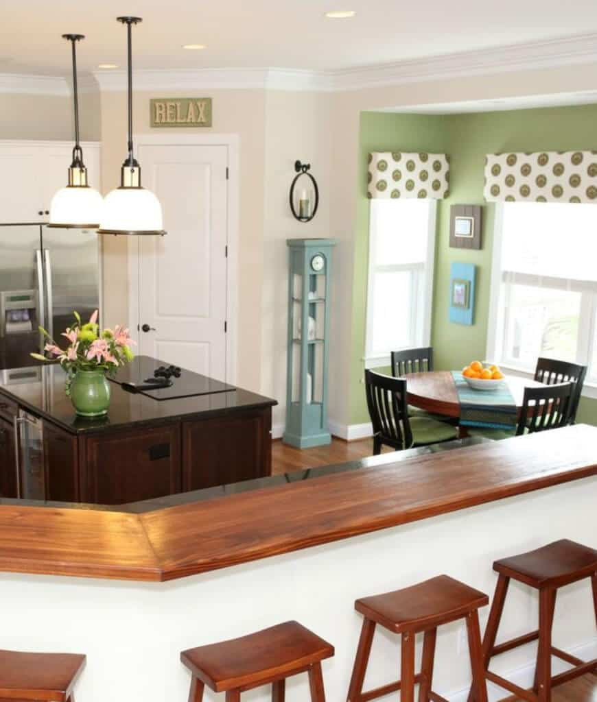 Fresh dine-in kitchen features a curved two-tier island bar and a dark wood central island lighted by a pair of pendant lights. It includes a round dining table and green cushioned chairs by the glazed windows dressed in dotted valences.