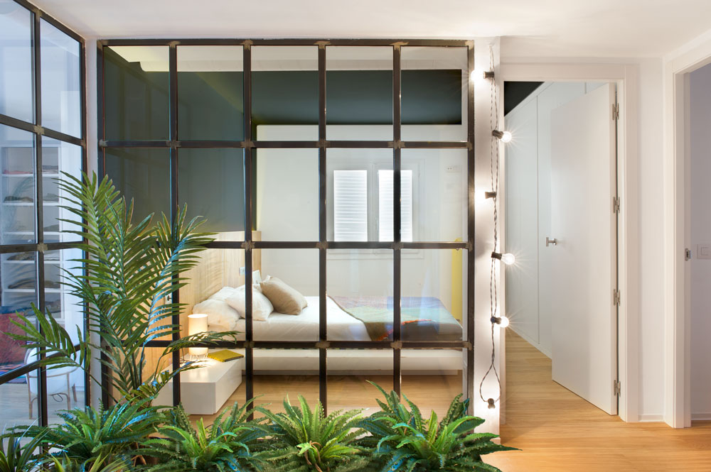 A view of the modern guest bedroom from the outside with hardwood flooring and black framed window lined with string lights.
