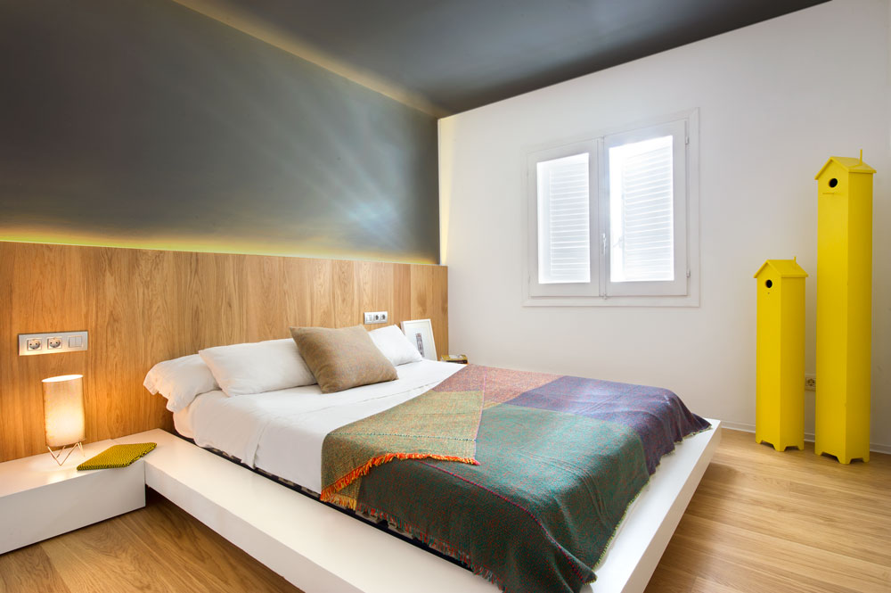Modern guest bedroom with a white built-in bed and nightstands fixed on the custom wood headboard. It has wide plank flooring and gray accent wall illuminated by strip lights.