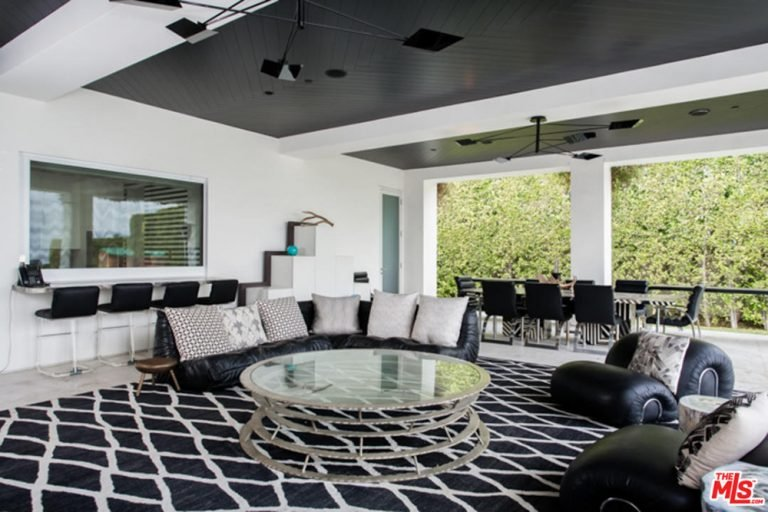 Large great room featuring a stylish tray ceiling and rug along with black elegant seats all over the place.