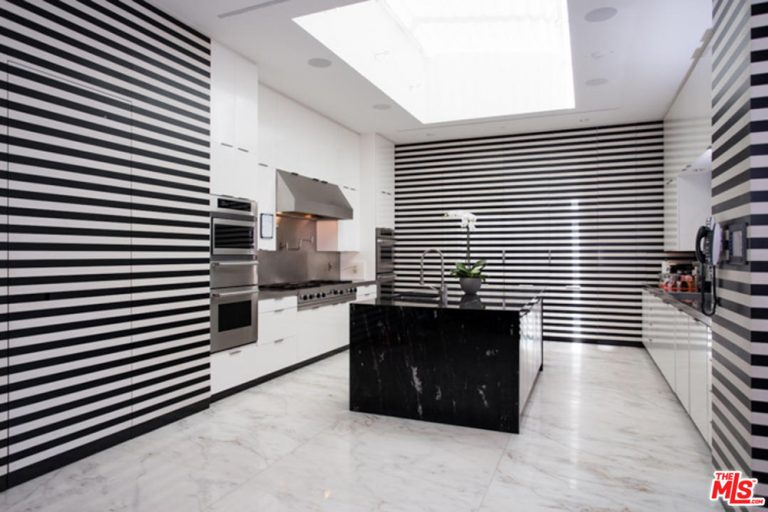Modern kitchen with stylish walls and center island. The smooth marble flooring looks lovely as well.