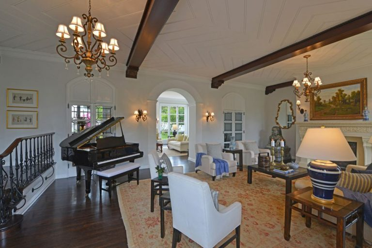 A second-floor formal living space featuring a piano on the side and a fireplace. The room is filled with warm white lights coming from the wall lights and chandeliers.