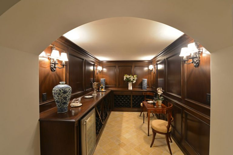 An arched open doorway leading to a dark wood wine cellar. It has an L-shaped counter and is illuminated by fancy sconces. Yellow brick floor tiles highlight the room.