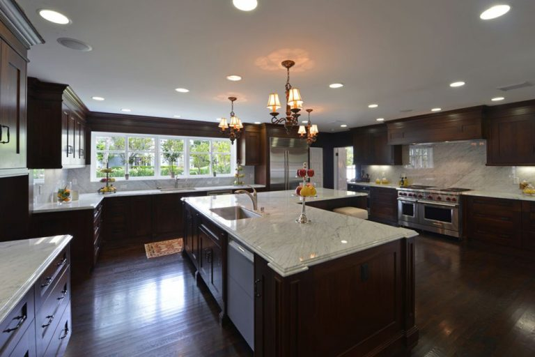 Darkwood kitchen brightened by recessed lighting, fancy chandeliers and atural light that comes from the glass windows. It features a huge L-shaped breakfast island topped with white marble and fitted with a sink and chrome faucet.