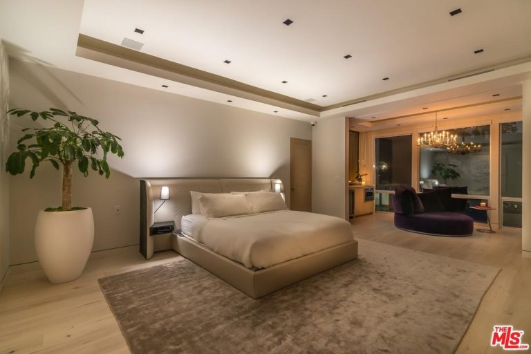 Large master bedroom featuring hardwood flooring and tray ceiling. There's a sitting area near the glass windows lighted by a glamorous chandelier.