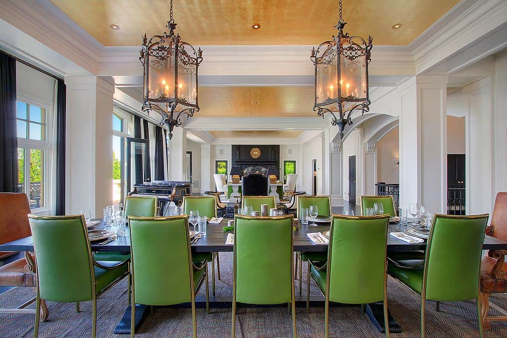 The green seats and dark-finished large dining table looks so classy. The area is lighted by two gorgeous chandeliers set on the tray ceiling.