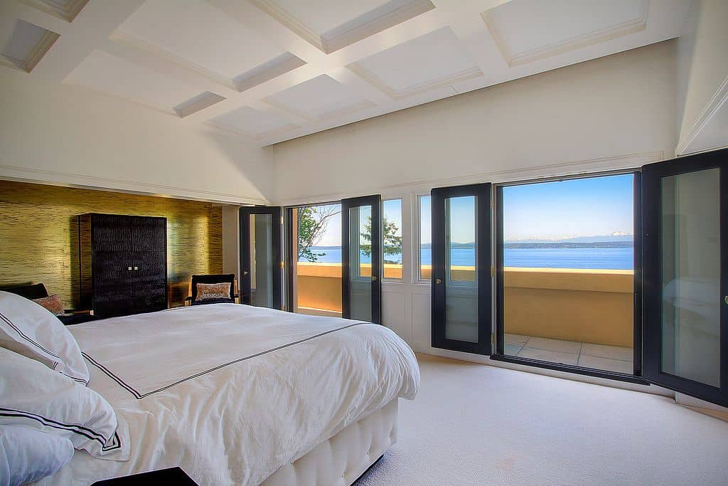 Spacious master bedroom with a large bed set on the white carpet flooring matching the white coffered ceiling.