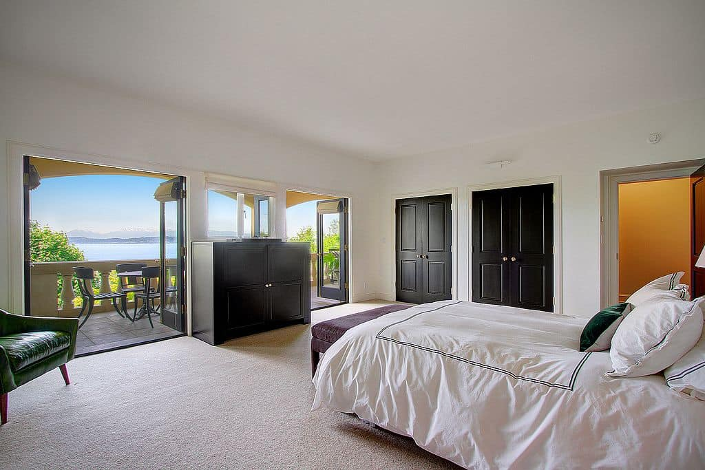 A master bedroom featuring white carpet floors and white walls along with a white ceiling. There are doorways leading straight to the balcony patio.